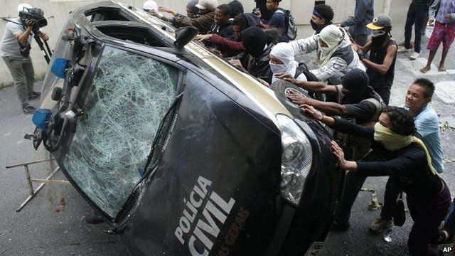 Protesters push over a badly beaten police car in in Belo Horizonte