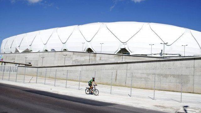 Andy Smith rides his bike past the Arena da Amazonia stadium