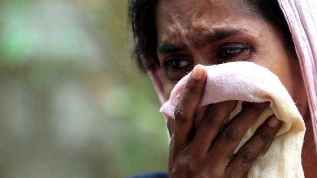 A Muslim woman cries next to her burnt house after a clash between Buddhists and Muslims in Aluthgama