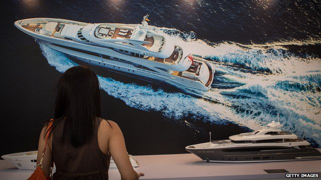 A woman looking at a yacht model