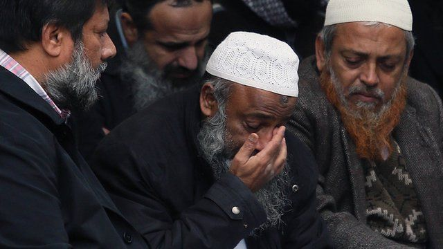 Dr Muhammad Taufiq Al Sattar (centre) prays over the coffins of his family in October 2013