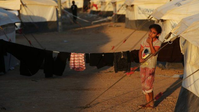 Girl standing in front of tent in refugee camp in Iraq