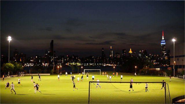 A football field in Brooklyn with Manhattan skyline behind