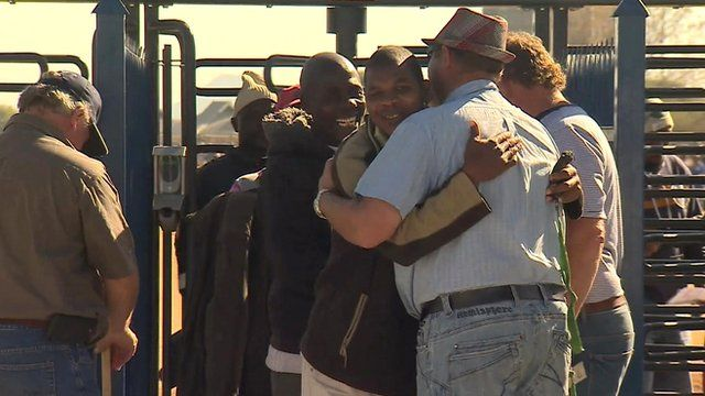 Miners greet each other as they return to work