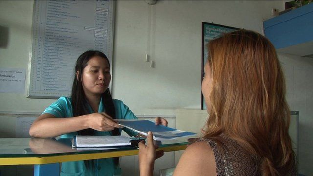 Nurse handing over leaflet to patient at counter