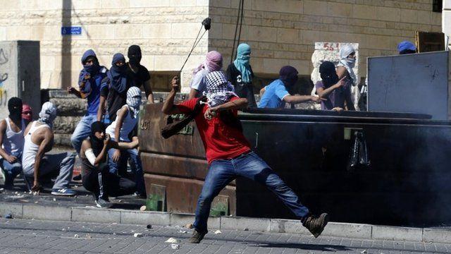 Palestinian hurling stone towards police