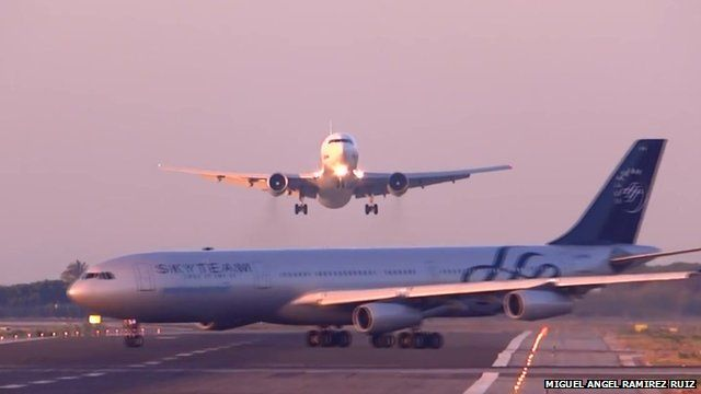 An Airbus 340 is shown crossing the runway at El Prat Airport as a flight from Moscow is coming in to land