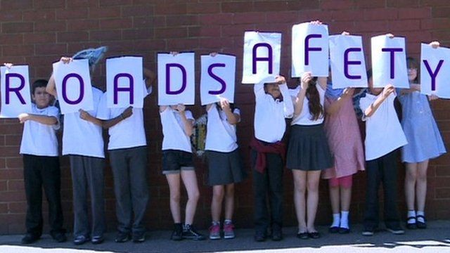 Children holding 'road safety' sign