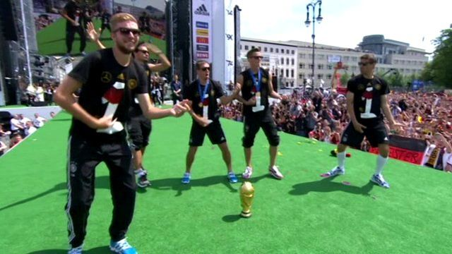 Germany team players dance on stage surrounded by hundreds of thousands of fans at the Brandenburg Gate, Berlin