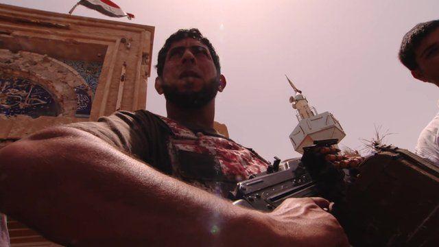 Man with gun below Iraq flag