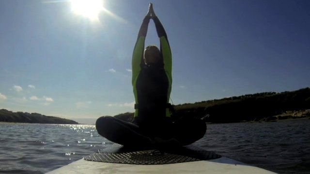 Woman in yoga position on a paddleboard