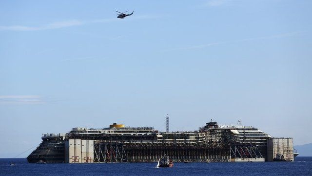 A military helicopter flies over the cruise liner Costa Concordia during refloat operation maneuvers at Giglio Island July 23, 2014