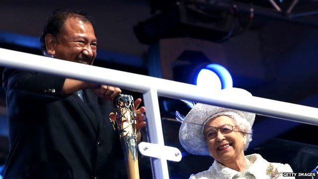Prince Imran the CGF President attempts to retrieve the message from the baton as he presents it to Queen Elizabeth II