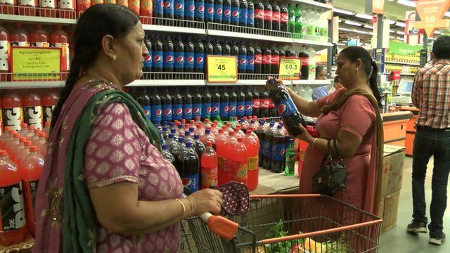 Indian women looking at fizzy drinks in a supermarket