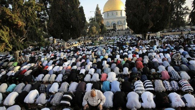 """Muslim worshippers take part in a prayer in front of the Dome of the Rock during the holiday of Eid al-Fitr on the compound known to Muslims as al-Haram al-Sharif and to Jews as Temple Mount in Jerusalem""""s Old City"""