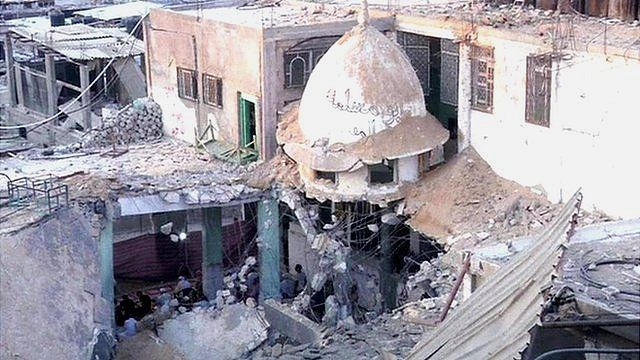 worshippers in ruins of mosque