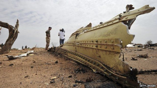 A French soldier and a journalist look at debris of the Air Algerie Flight AH 5017 scattered at the crash site