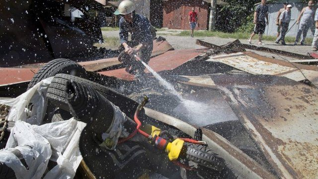 A fireman extinguishes a destroyed garage the after shelling in Donetsk