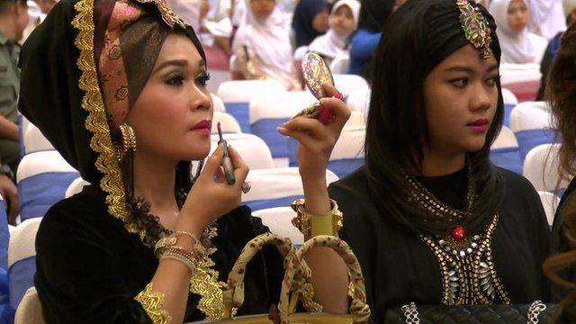 Smartly dressed woman applying lipstick and sitting with a friend