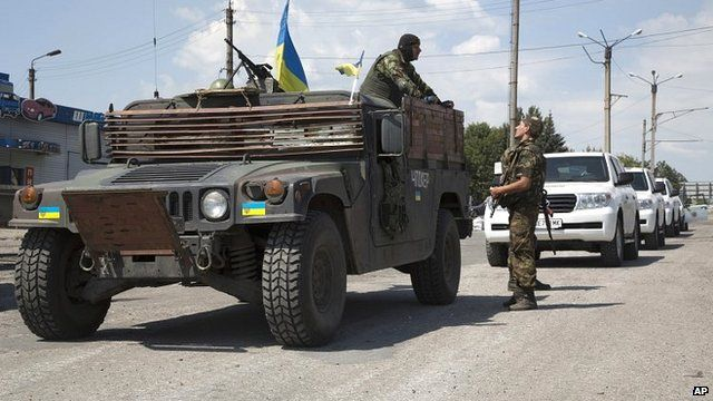 Ukrainian government army's soldiers stand guard next to the cars of convoy of the OSCE mission in Ukraine