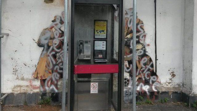 """Defaced Banksy """"Spy Booth"""" mural"""