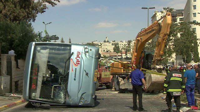 Digger and overturned bus