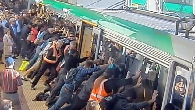 """A frame grab from a video released on August 6, 2014 from the Public Transport Authority of Western Australia shows commuters pushing a train to free a passenger's leg trapped between the train and the gap in Perth. Dozens of Australians tilted a train to free a commuter whose leg was trapped between a carriage and a platform, with authorities praising their efforts as an example of """"people power""""."""