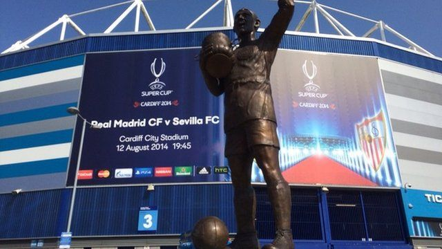 The Fred Keenor statue outside the Cardiff City stadium in front of the banner for the Uefa Super Cup