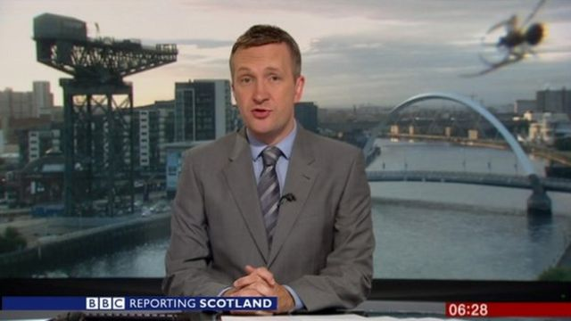 News reporter and spider in the corner of the screen