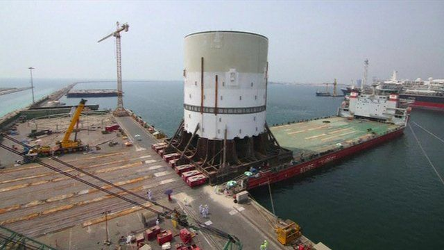 Still from time-lapse footage shows the largest piece of the turret being moved onto a barge
