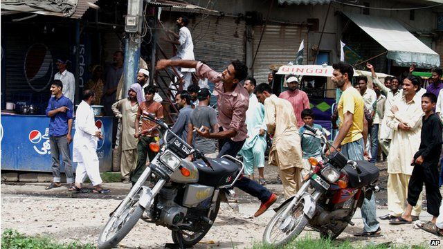 One of the supporters of Pakistan's ruling party throws a rock on a procession of cricketer-turned-politician Imran Khan in Gujranwala, Pakistan