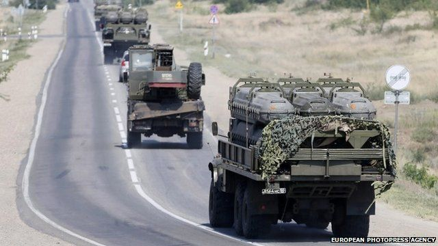 Russian armoured vehicles move along a road outside the town of Kamensk-Shakhtinsky in Rostov region, in Russia