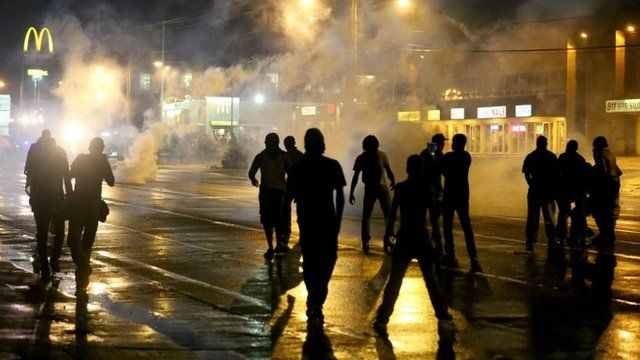 People are seen as police start to fire tear gas at a demonstrators protesting the shooting death of Michael Brown