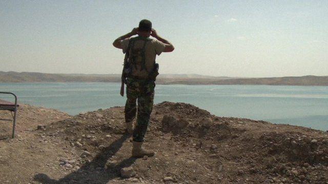 Kurdish soldier surveys dam