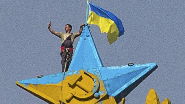 """A man takes a """"selfie"""" as he stands with a Ukrainian flag on a Soviet-style star"""