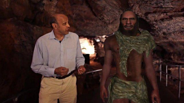 Pallab Ghosh walking next to simulation of a Neanderthal man