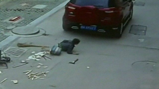 A car drives off after running over a boy in China