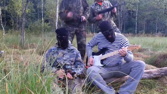 Masked men in military uniforms, one playing a guitar.