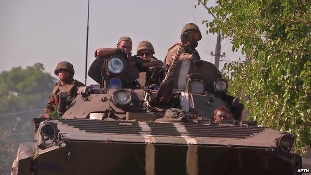 Ukrainian soldiers in a tank leaving through 'humanitarian corridor' as pro-Russian rebels advance