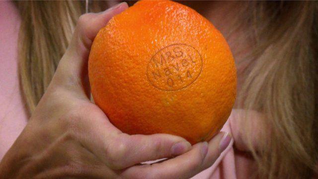 An orange labelled using a laser machine