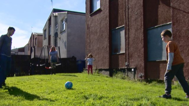 Family surrounded by derelict housing