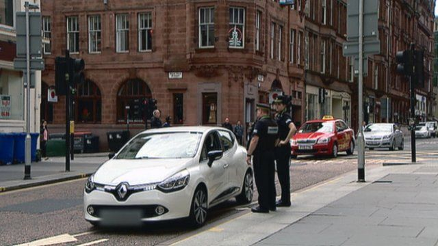 Police stop a driver in a bus lane