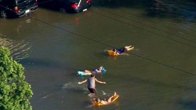 People on lilos in flooded street