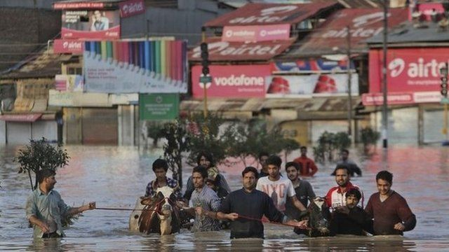 In Kashmir, residents have waded through neck-deep waters with their belongings.