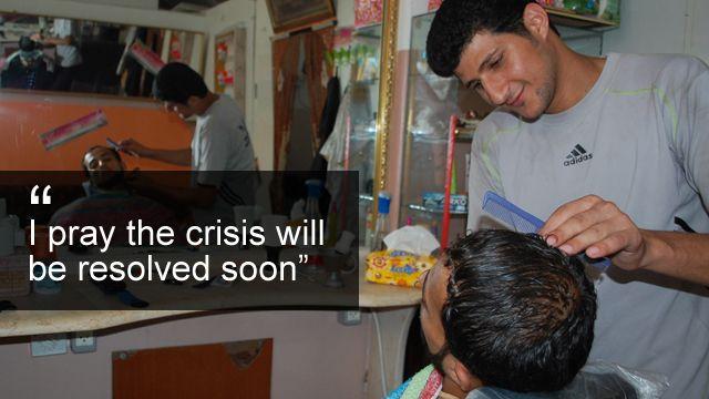 Barber Essam Habib serves a customer