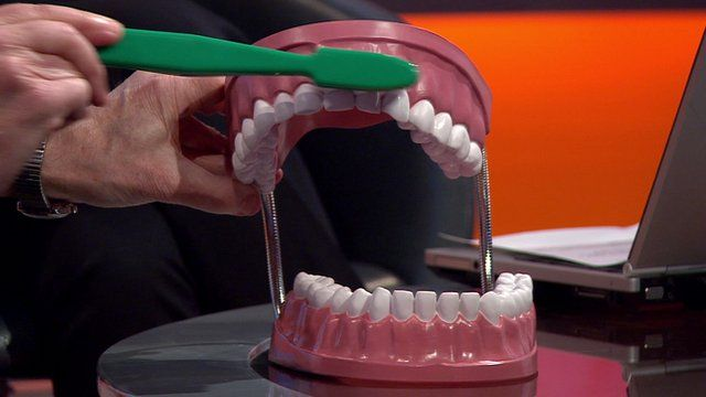 Professor demonstrating proper way to brush your teeth