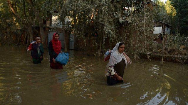 Kashmiri residents wade through floodwaters in Rakshalana south of Srinagar