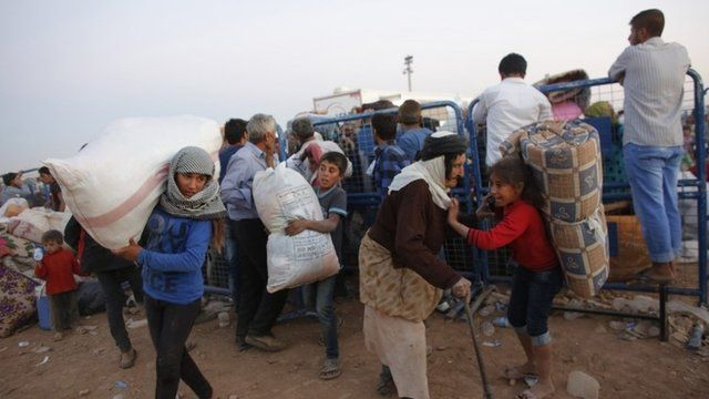 Newly arrived Syrian Kurdish refugees carry their belongings after crossing into Turkey