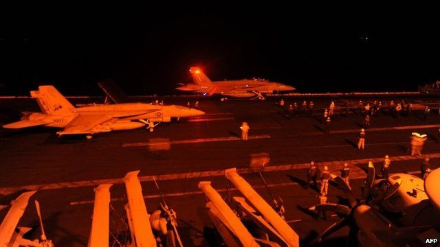 Fighter jets prepare to launch from the flight deck of a US aircraft carrier