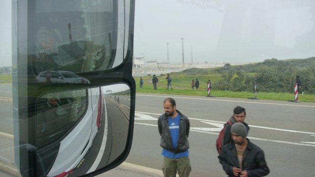 View from driver's window of migrants on road